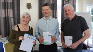 Three people smiling holding certificates