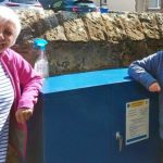 Two woman standing beside a blue box
